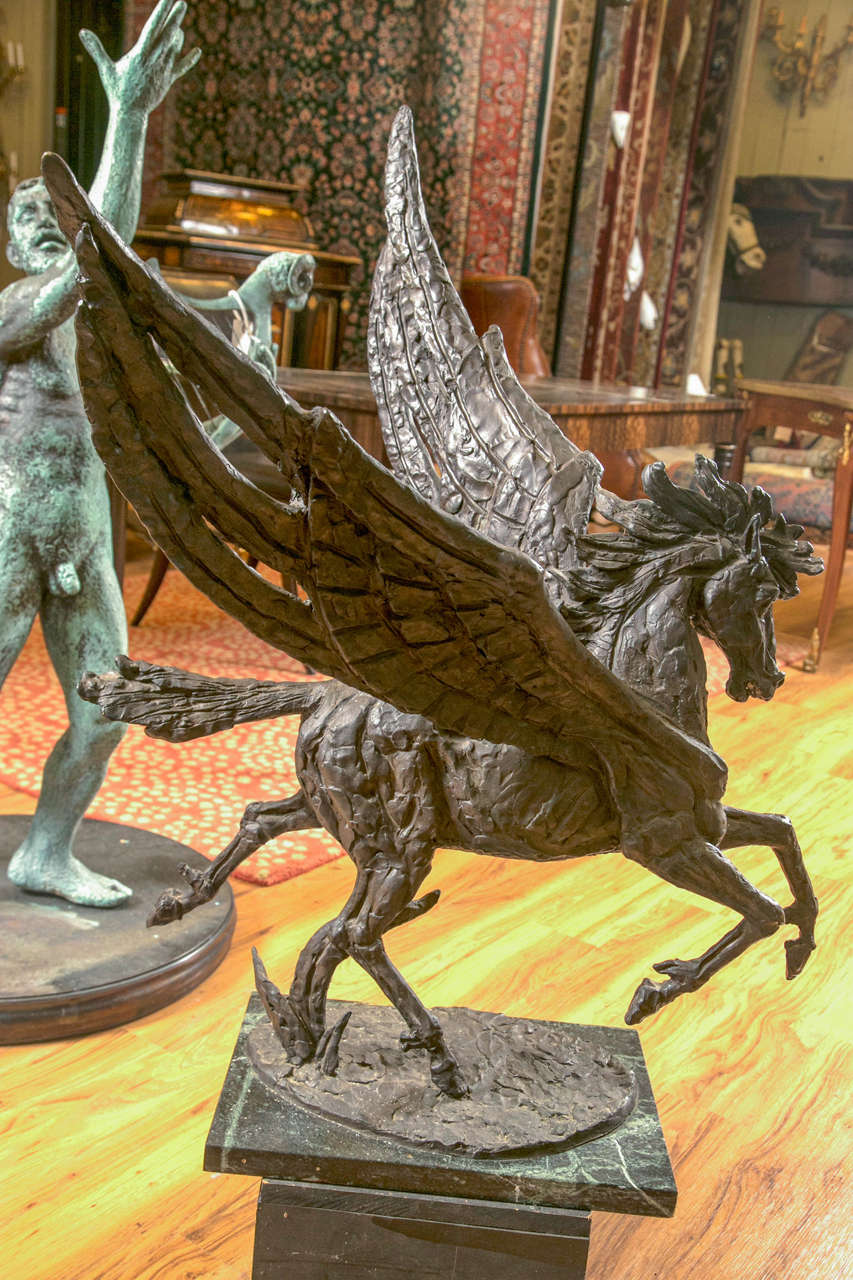 Intricately detailed mythological winged Pegasus. Variations in patina throughout. Stands on a contemporary marble base. This large stallion with wings is bronze and signed by Laszlo Ispanky. Pegasus' have been a mainstay of fantasy art and called