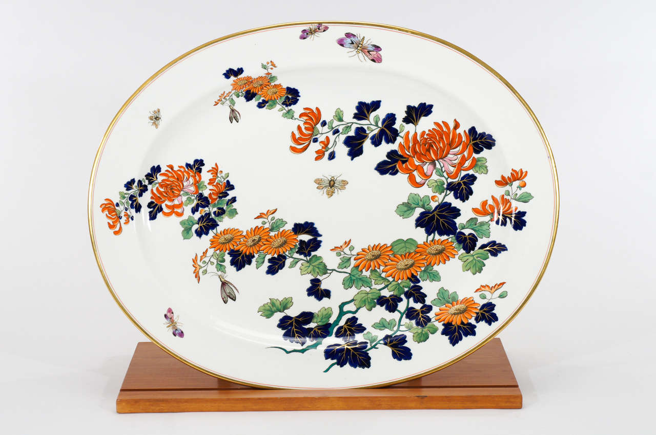 Spectacular large oval porcelain platter with hand painted polychrome enamel decoration in the Imari palette. This beauty is embellished with gold trim and highlighted with bees and butterflies in the