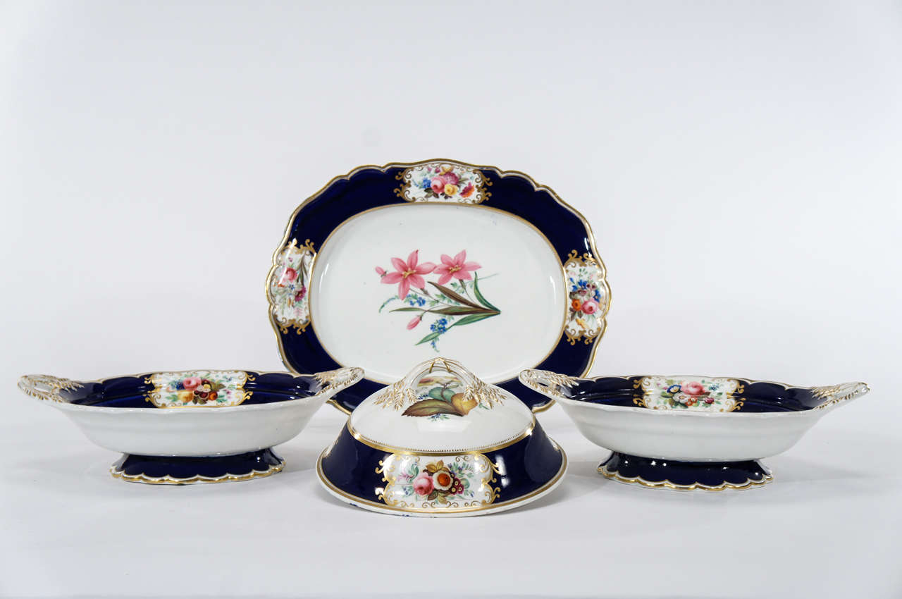 This is a lovely grouping of early 19th C. English hand painted botanical serving pieces.  Each piece is embellished with cobalt borders, shaped rims and gold trim and the vegetable tureens have the added decorative element of detailed wheat sheaves