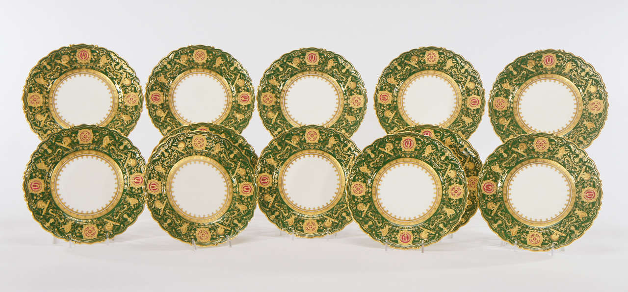 Set of 12 Coalport shaped rim green dessert plates with profuse raised paste gold depicting neoclassical motifs and musical Instruments. The forest green ground is embellished with four reserves in a ruby red with detailed neoclassical raised gold