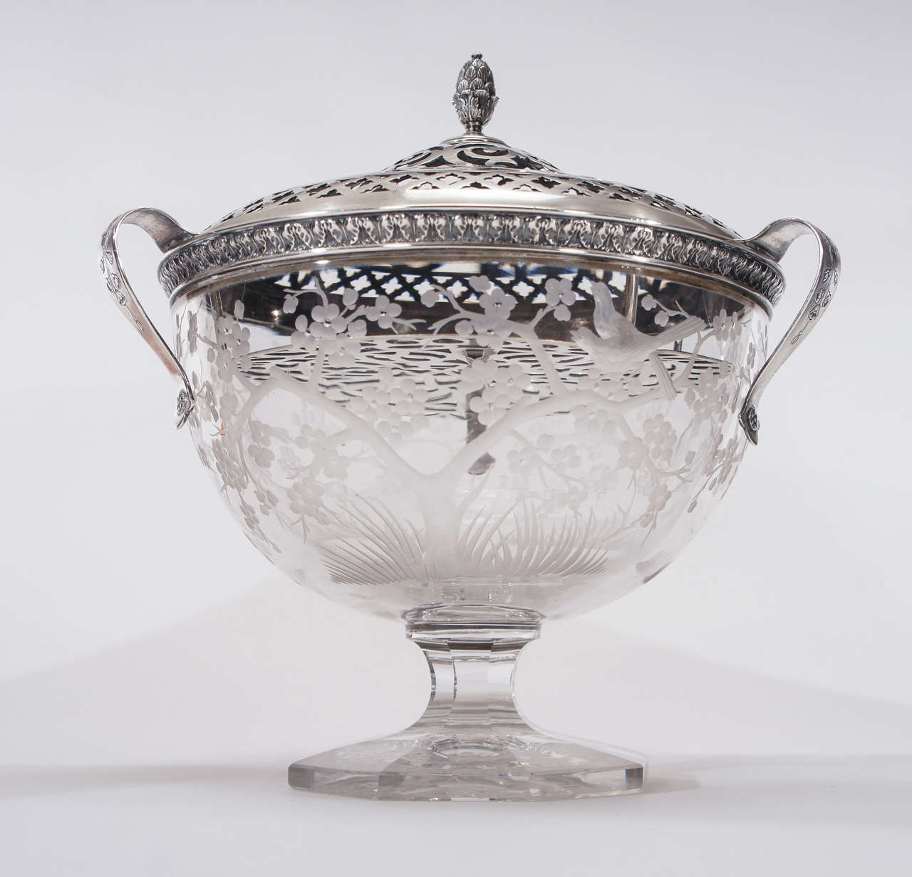 A rare and perhaps unique footed centerpiece most certainly made by Hawkes in Corning NY. in the Aesthetic Movement style. The heavy crystal is decorated with copper wheel engraved birds and  cherry blossoms and sits on an octagonal base. The bowl