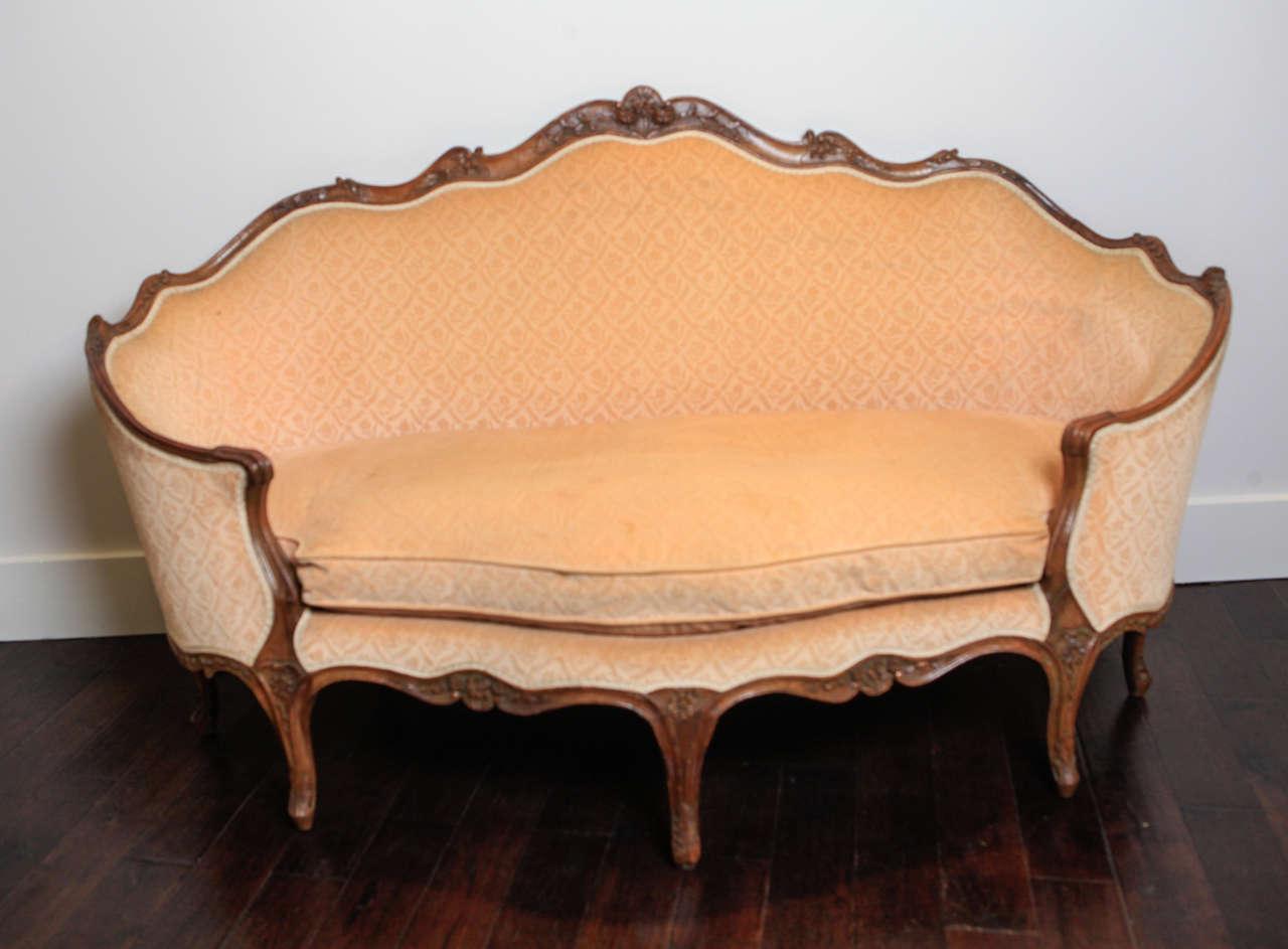 Carved frame sofa is upholstered in French gaufrage velvet.