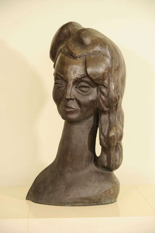 A fine solid bronze bust sculpture of a woman with an elongated next and stylized hair with a floral comb similar in feeling to the femme fatales of Tamara Lempika and self portraits of Frida Kahlo.