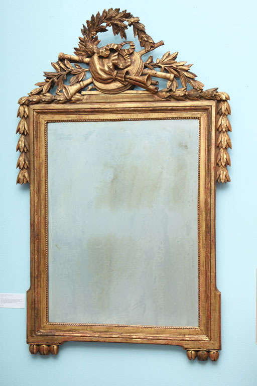Neoclassical style frame of carved and giltwood with large, central antique mirror. The carved top features a musical trophy, laurel wreath, branches and bell flowers draped over the corners. Bottom corners feature carved bulbs.