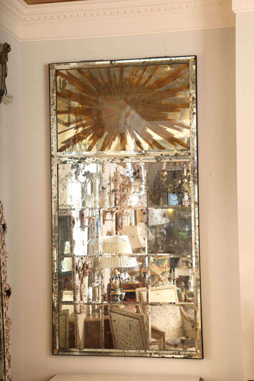Mirror, of large scale, having twelve beveled panels of spotted mirror in mirrored frame, surmounted by reverse painted sunburst design.