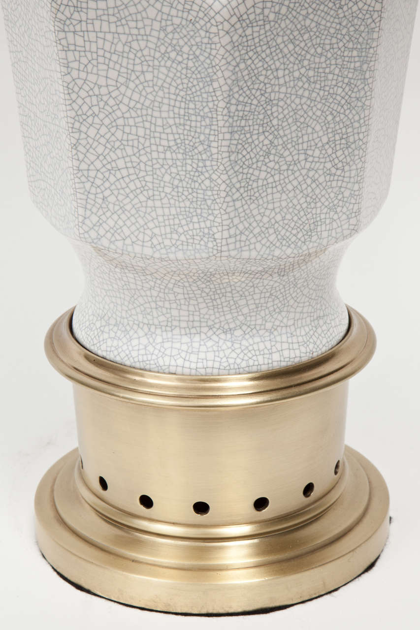 Pair of classically styled crackled glazed ceramic lamps on satin brass bases and hardware.