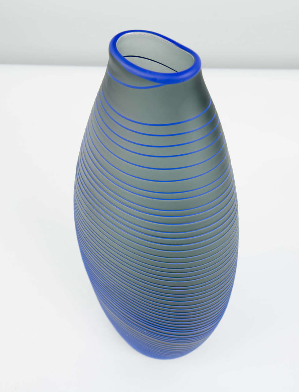 Tonal Frequency Vase in Grey is a unique handblown glass vessel with fine raised cane detail created by the British artist Liam Reeves. Handblown in grey glass, the exterior surface has a blue glass trail that winds around the entire piece, ending