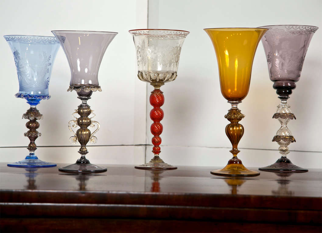 Magnificent etched and blown Venetian glass goblets by Gianni Seguso, Vetro Artistco Murano.   5 Available  1. Goblet with ruby stem, birds, and grape vine - $1,495.00 2. Amber goblet with gilt stem - $750.00 3. Goblet with blue cup, putti,