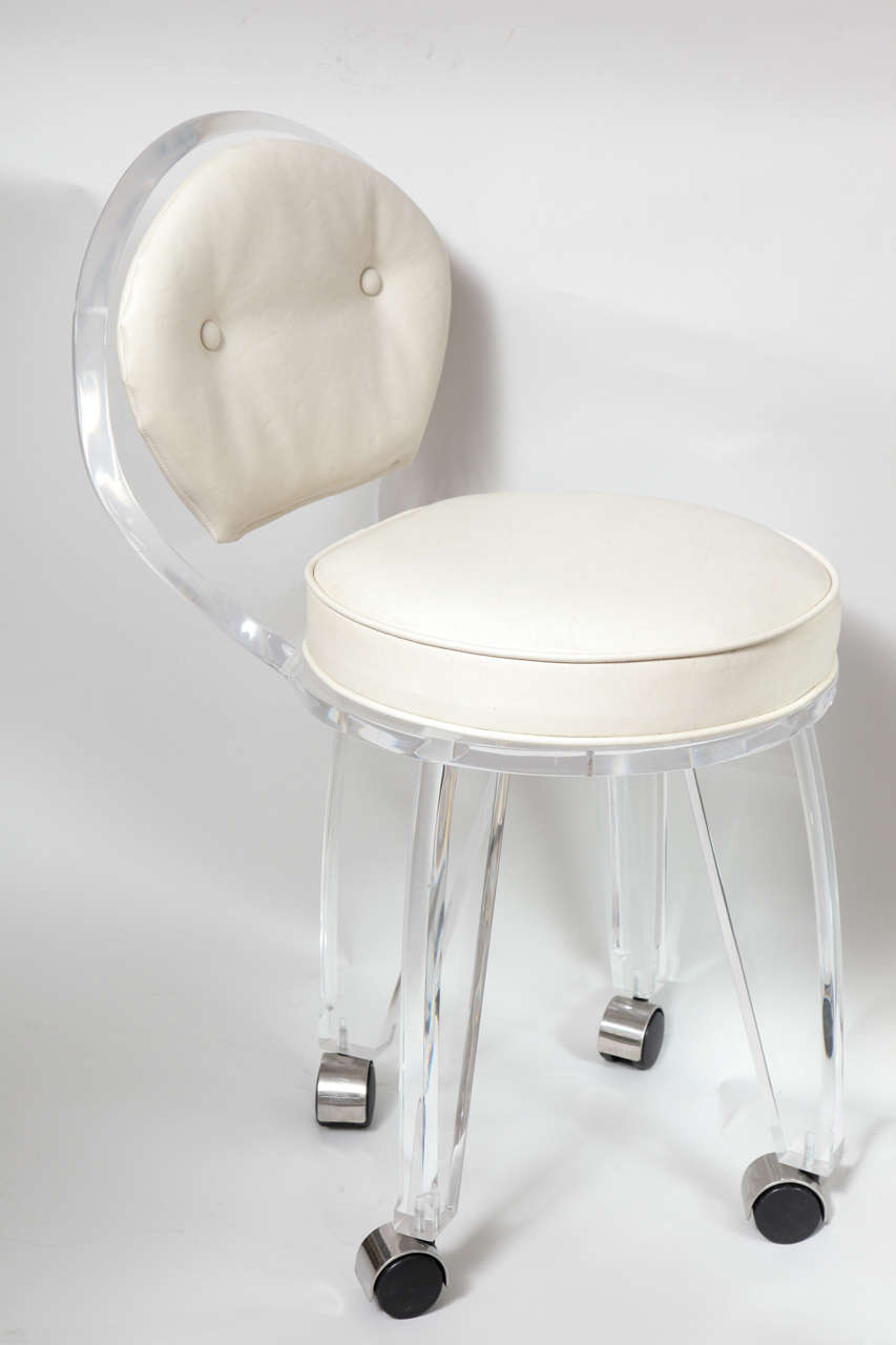 An elegant vintage Lucite vanity swivel chair with white vinyl upholstery. This practical piece would work great for any vanity or desk and is on a good set of rolling casters.