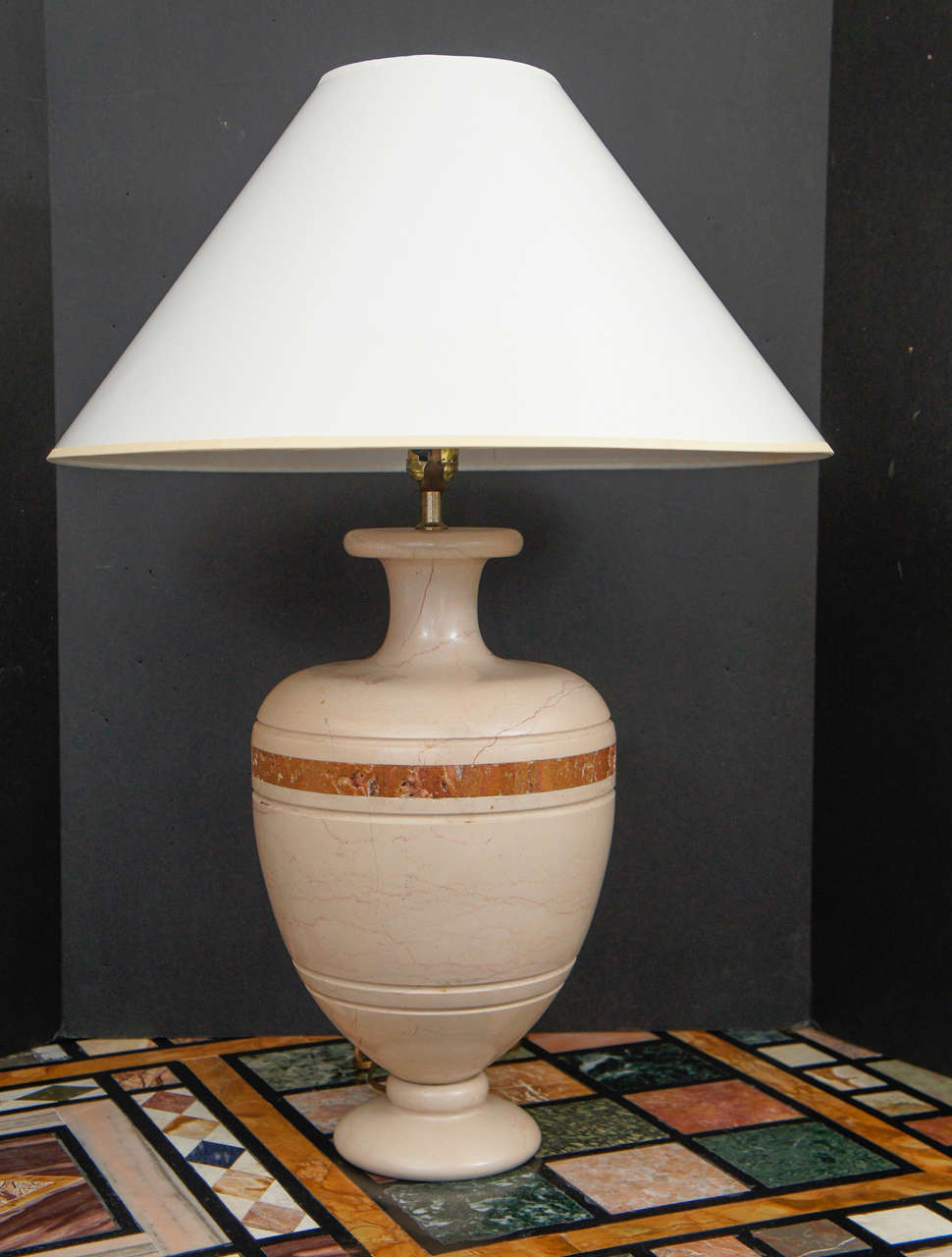 This pair of vintage 1970s Italian table lamps are made from carved travertine that has been inlaid with a rouge marble band. Carved from a solid block the lamps are very substantial and heavy. Travertine a stone favored by the Romans and here used