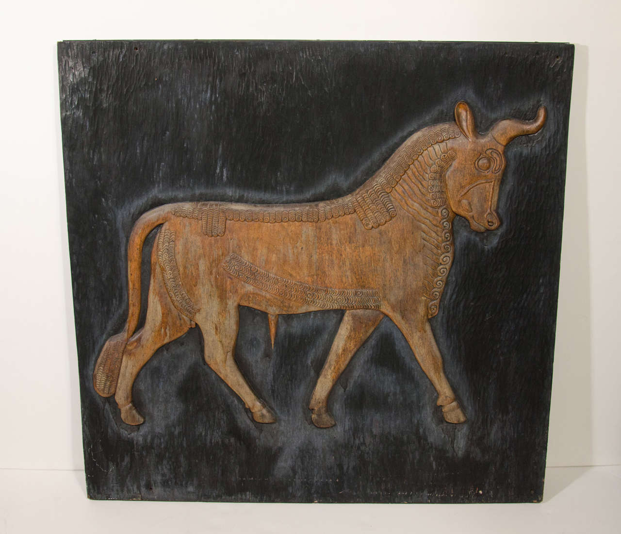 Rare artwork featuring Arabic bull in hand-carved reclaimed wood with exquisite attention to form and detail. Highly stylized engraved bull with decorative carvings over wood panel with hand chiseled grooves throughout. The bull has tones of faded