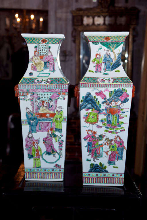 A TALL PAIR OF CHINESE PORCELAIN VASES, HAND PAINTED WITH COURTLY SCENES AND LION FORM MASKS AND RINGS