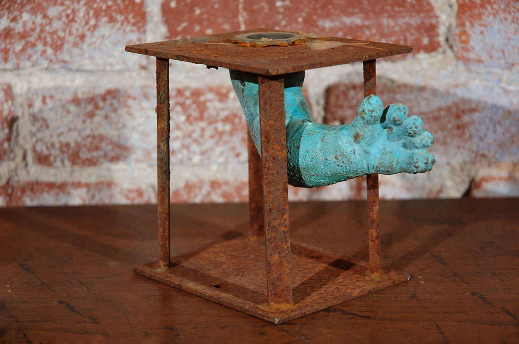 Baby doll arm mold from a toy factory in the bronx.  Arm  reaches out past original manufacturing apparatus.  Layered and patinated surface due to exposure to various chemicals and high heat during the manufacturing process.  Great bookshelf piece.