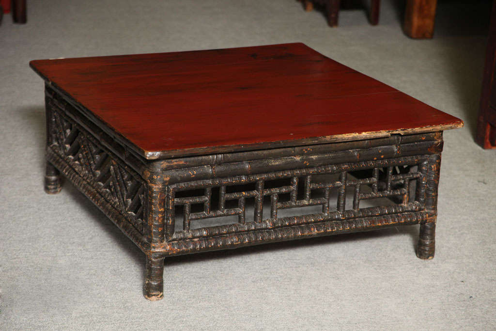 A petite Chinese 19th century coffee table made of bamboo with red lacquered square top. This low coffee table comes from China, where it was made with bamboo and lacquered wood during the 19th century. The top is nicely varnished with a red