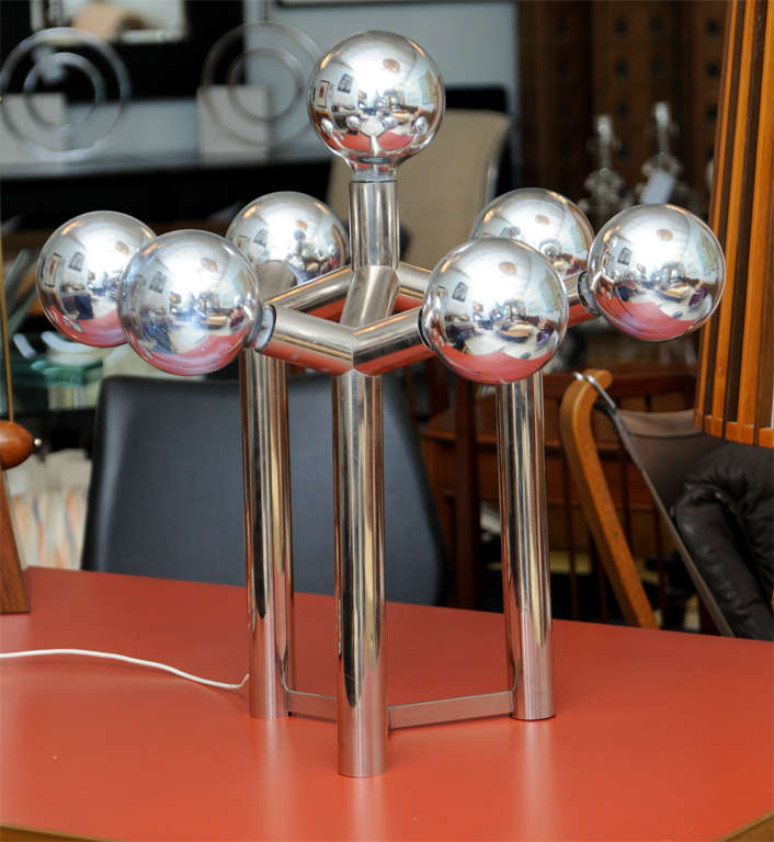 The mirrored globe bulbs in atomic configuration over a chrome base.