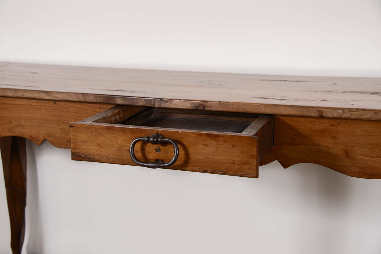 19th century narrow French cherry console or server with carved frieze all the way around. One drawer, circa 1870.