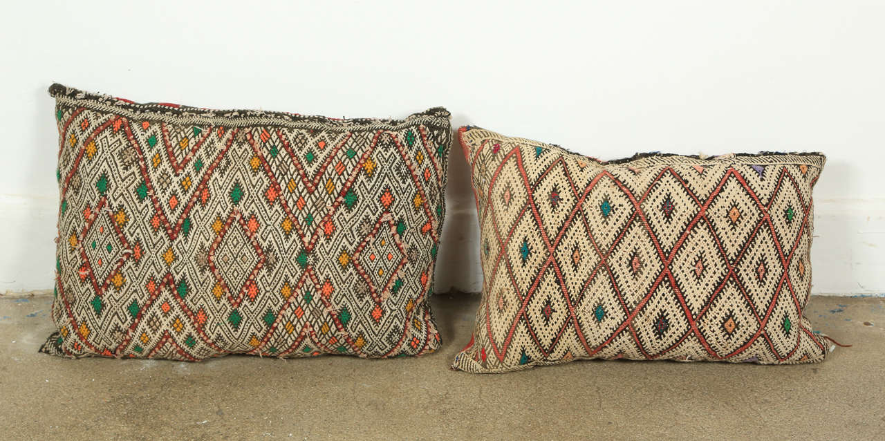 Handwoven tribal throw pillows made from vintage rugs. The front and the back are made from a different rug, front is more elaborate and back is striped. Measures: One pillow with red and black back is 21