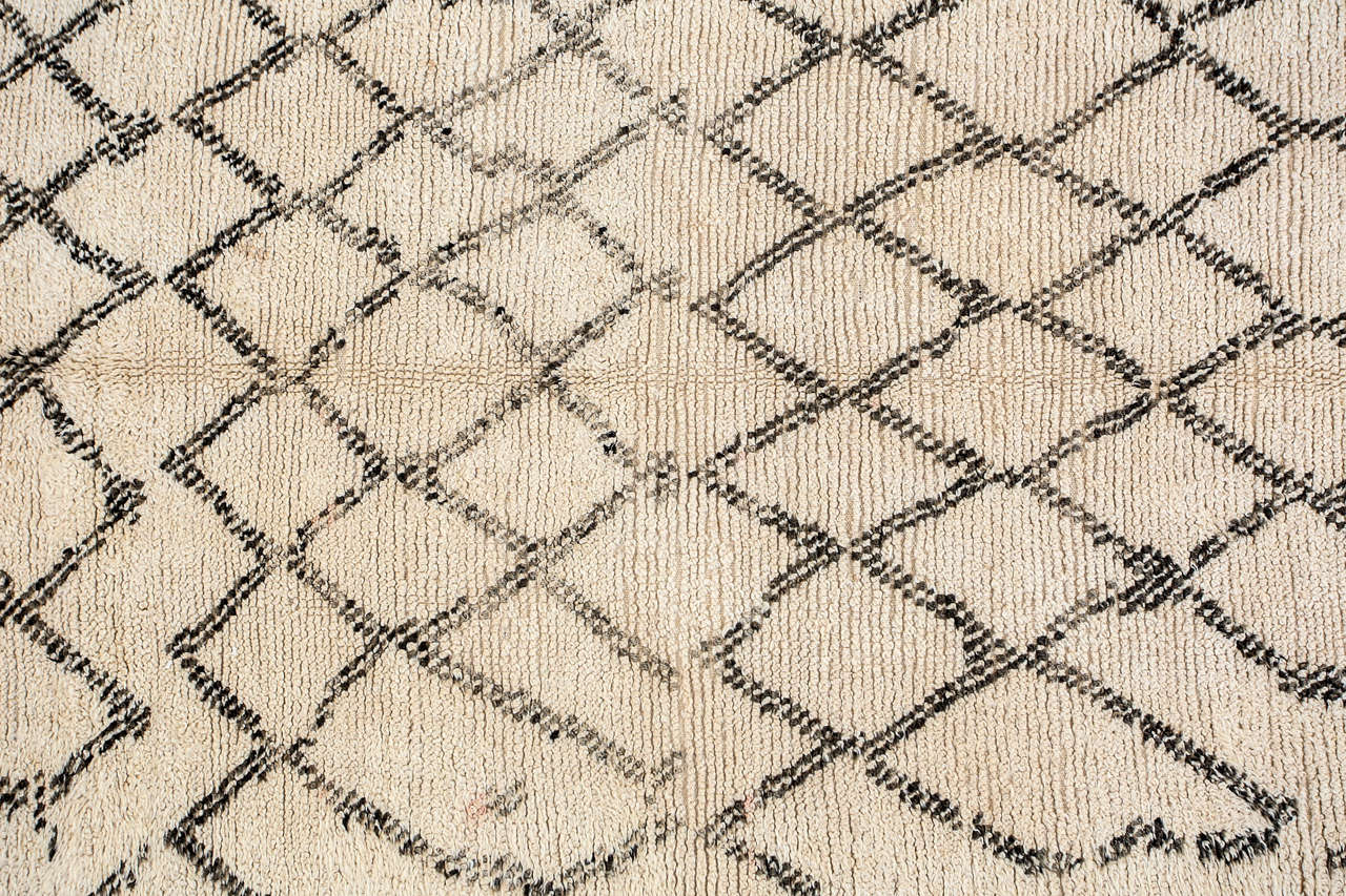 Moroccan vintage Berber rug from the Beni Ouarain tribes.  Lush white and black organic wool rug with geometrical lozenges designs. Dark black abstract designs in lozenges on a natural cream field lush lamb un dye wool. Very interesting modernist