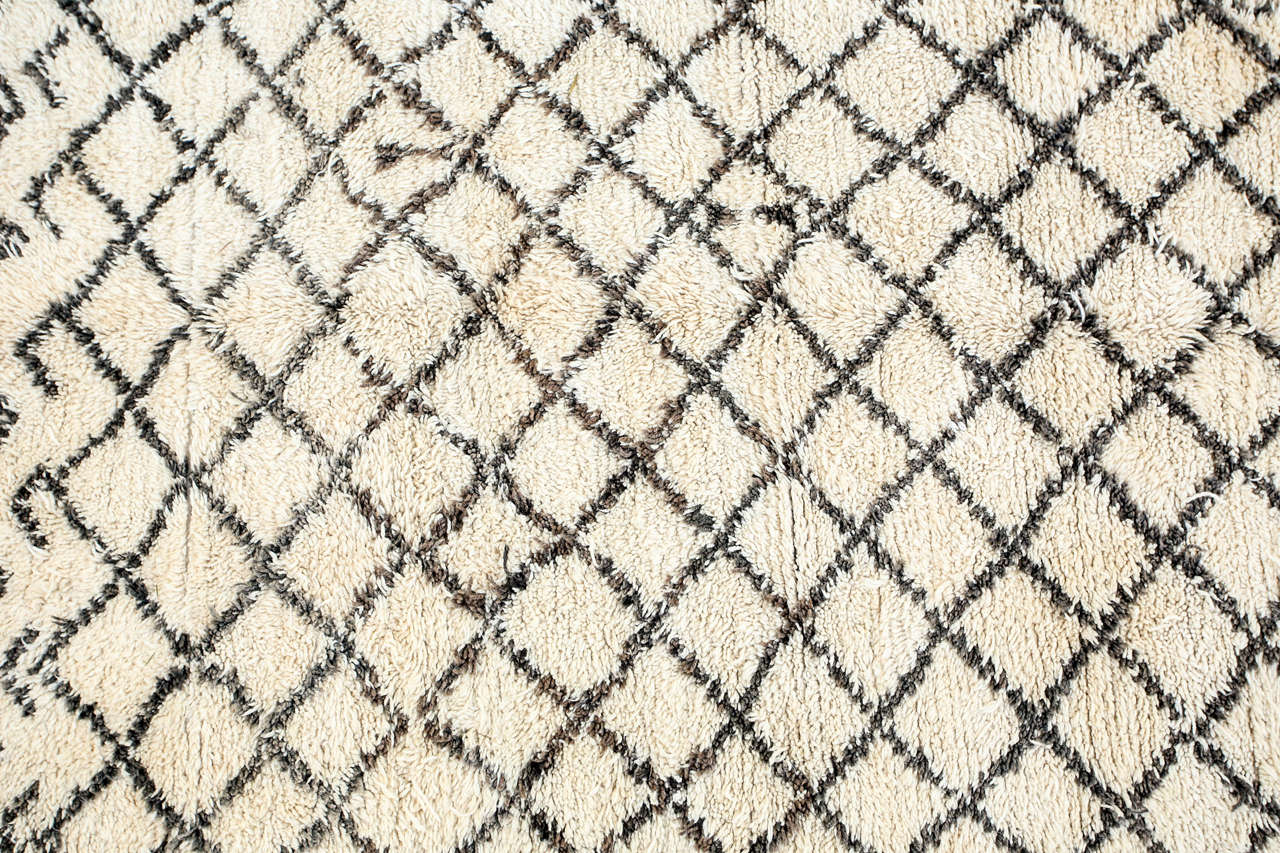 Moroccan Berber rug from the Beni Ouarain tribes. Lush white and black organic wool rug with geometrical lozenges designs. From the Middle Atlas Mountains. Circa 1950's.  North Africa. Dark black abstract designs in lozenges on a natural cream field