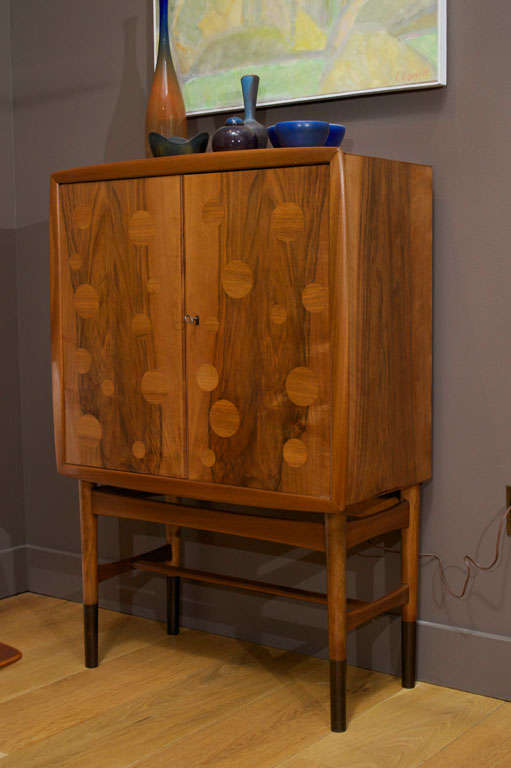 Bar cabinet of walnut by Gustav Bertelsen & Co. Cabinet features two doors concealing a lighted interior with two shallow shelves and one full shelf, two drawers and one pullout surface. Rear mirror in back of cabinet has been removed.