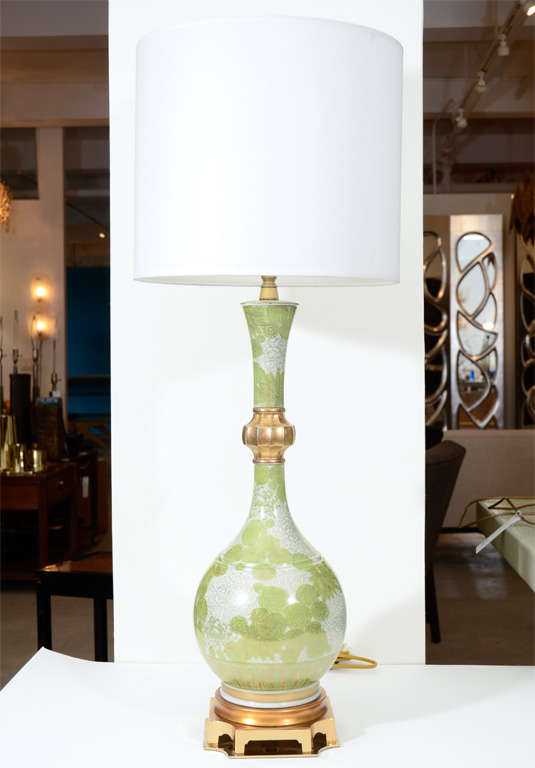 Exceptional pair of porcelain lamps depicting white and green chrysanthemums with gilt accents and gilt bronze bases.