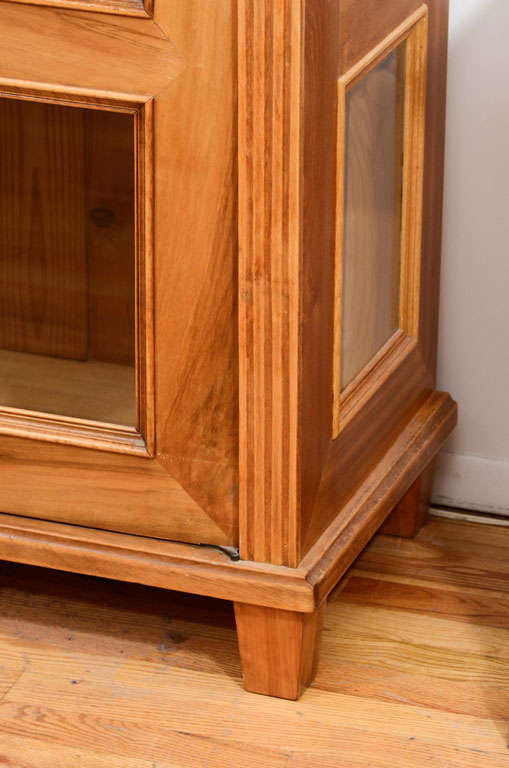 A dismountable display cabinet, with three thick glass shelves and eight panels of glass in the doors and sides, allowing viewing from three perspectives. A straight cornice rests above the walnut veneered case with flat Persian columns headed by