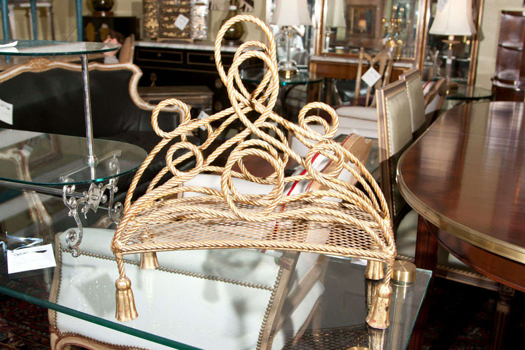 A Hollywood Regency style bronze magazine rack. Fine tassle form feet leading to a inticate rope design.