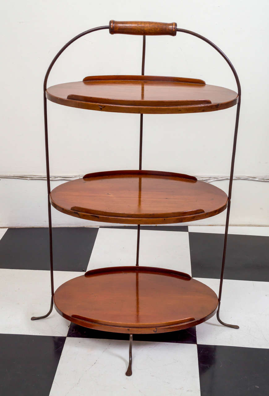 19th century English petite three-tier server. The three mahogany trays each fitted with small front and rear galleries. All of the trays are joined by brass legs that terminate with a wood handle on top and the bottoms splay out in wrought splayed