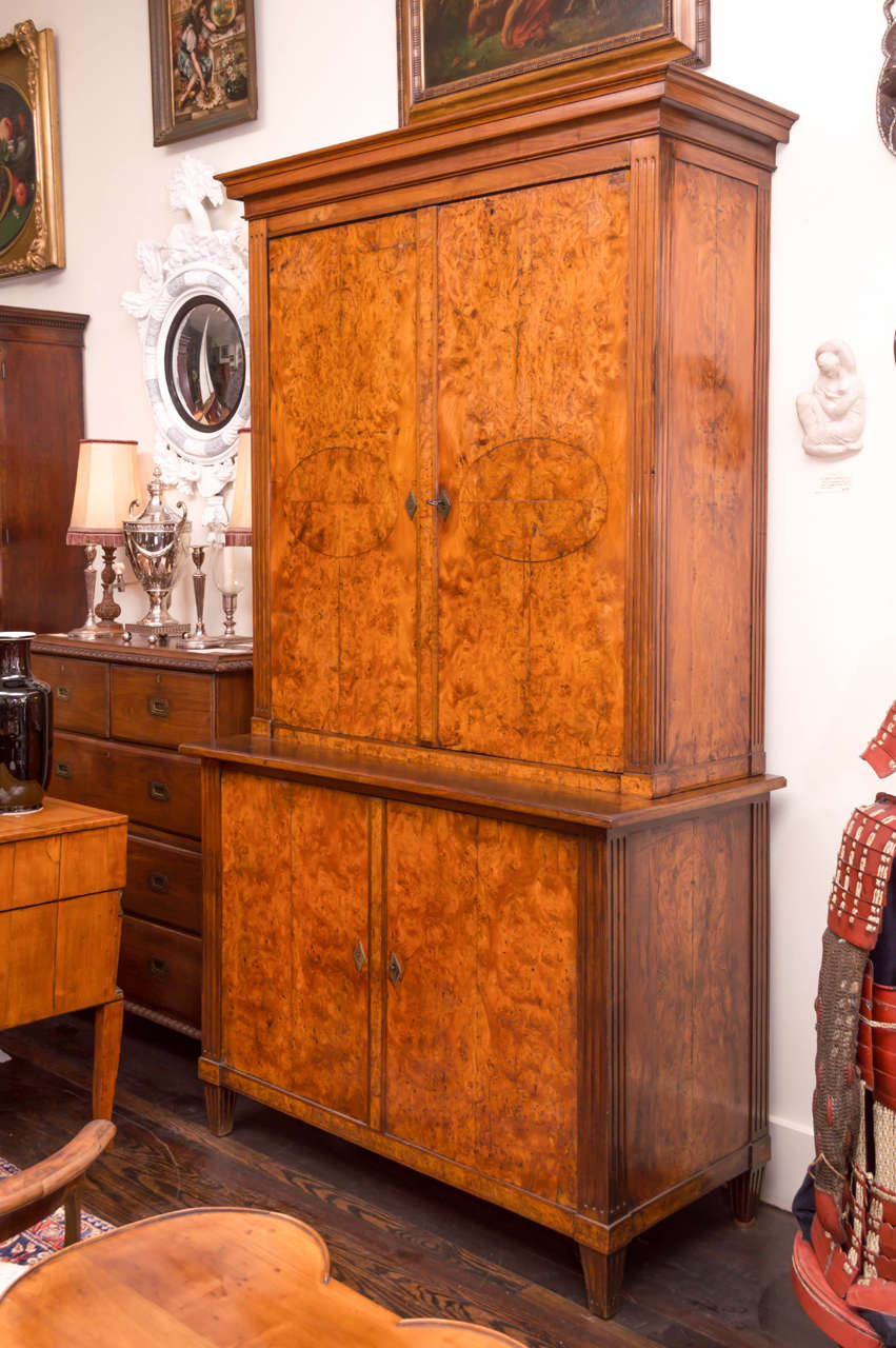 19th century German burr elm Biedermeier cabinet. Two sections, both fitted with shelves and an old white washed interior. Original hardware and locks. All book matched thick veneers on the doors and full sides. The fully figured veneers retain an