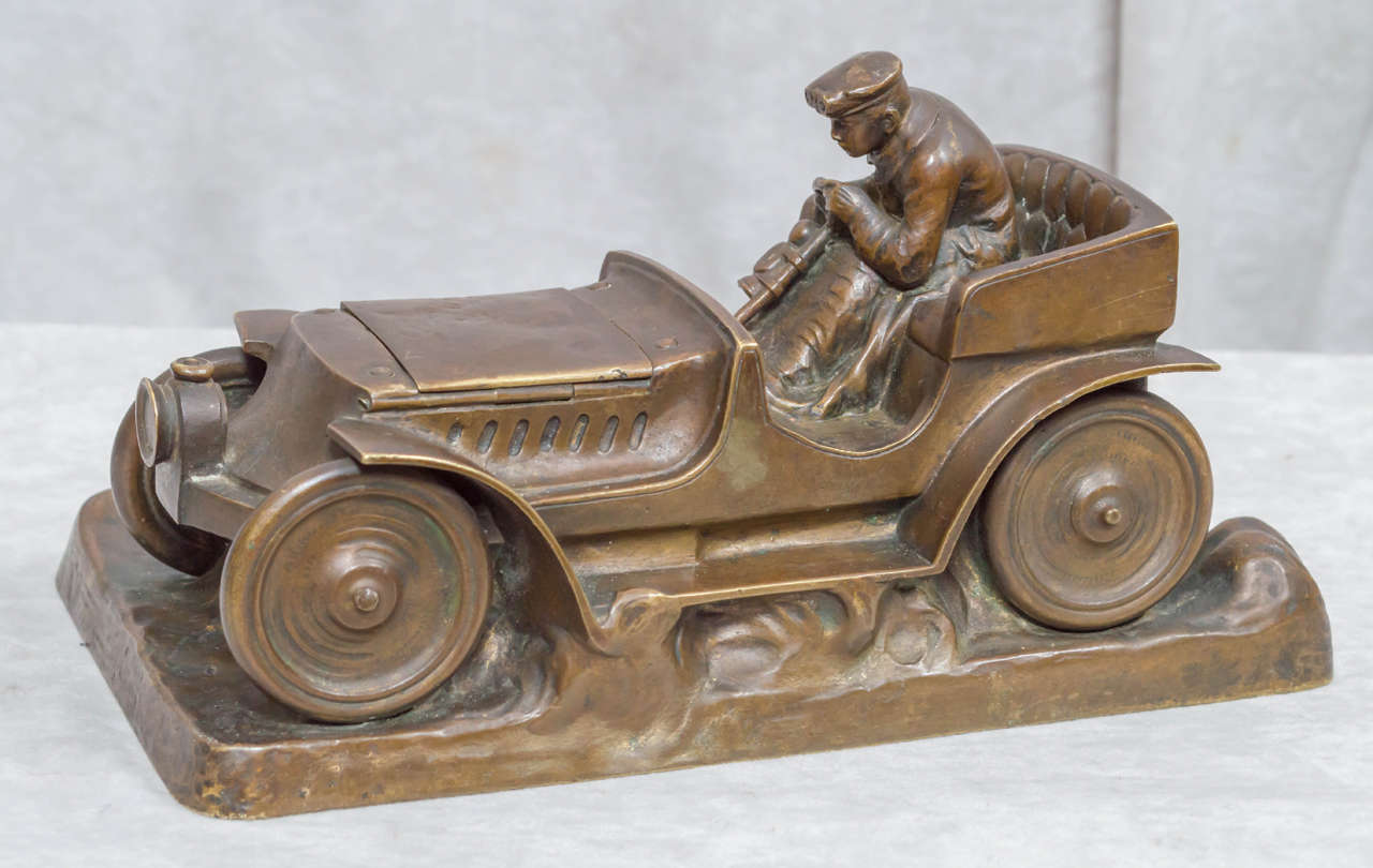 Oh how rare this subject matter in sculpture appears. We would like to point out that this no small trinket. It is impressive and good sized. The driver is a kick and the car is certainly from the period. The hood opens up to reveal an inkwell. A