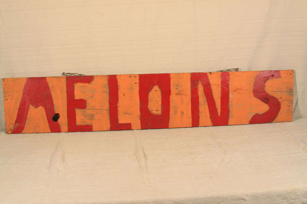 Charming and primitive, this wood sign is from a Texas roadside fruit stand and dates to the 1960s. Crude hand-lettering in bright red over a soft pumpkin-color background, this piece is sized right for a casual kitchen wall or along side other