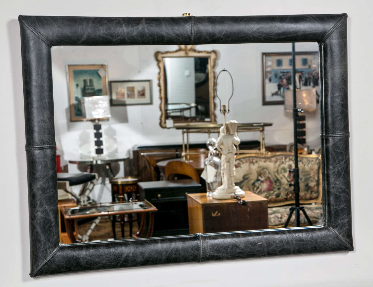 The rectangular glass surmounted on a dark charcoal color distress leather upholstered frame.