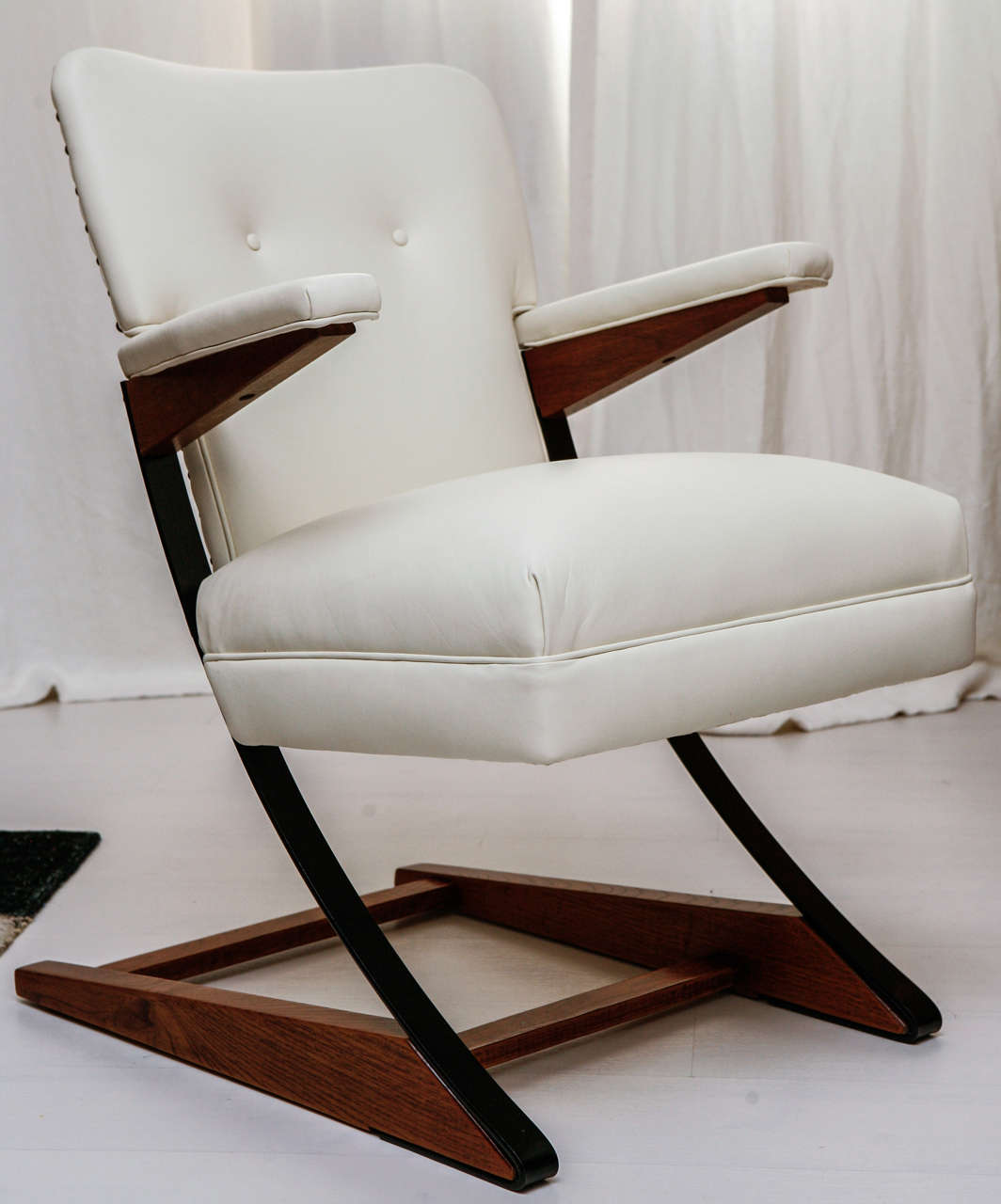 Boasting a modern white upholstery with grommets all along the backside's edge and a pair of button tufts on the frontside of the chair, this 1960s rocker is a rare and wonderful piece! The frame is a combination of steel and wood and the rocking