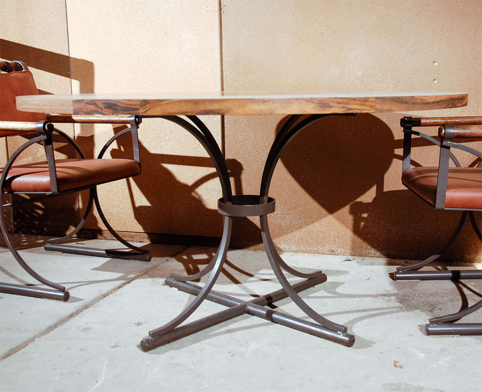 Five-piece dining set of chairs and table in iron, wood and naugahyde.