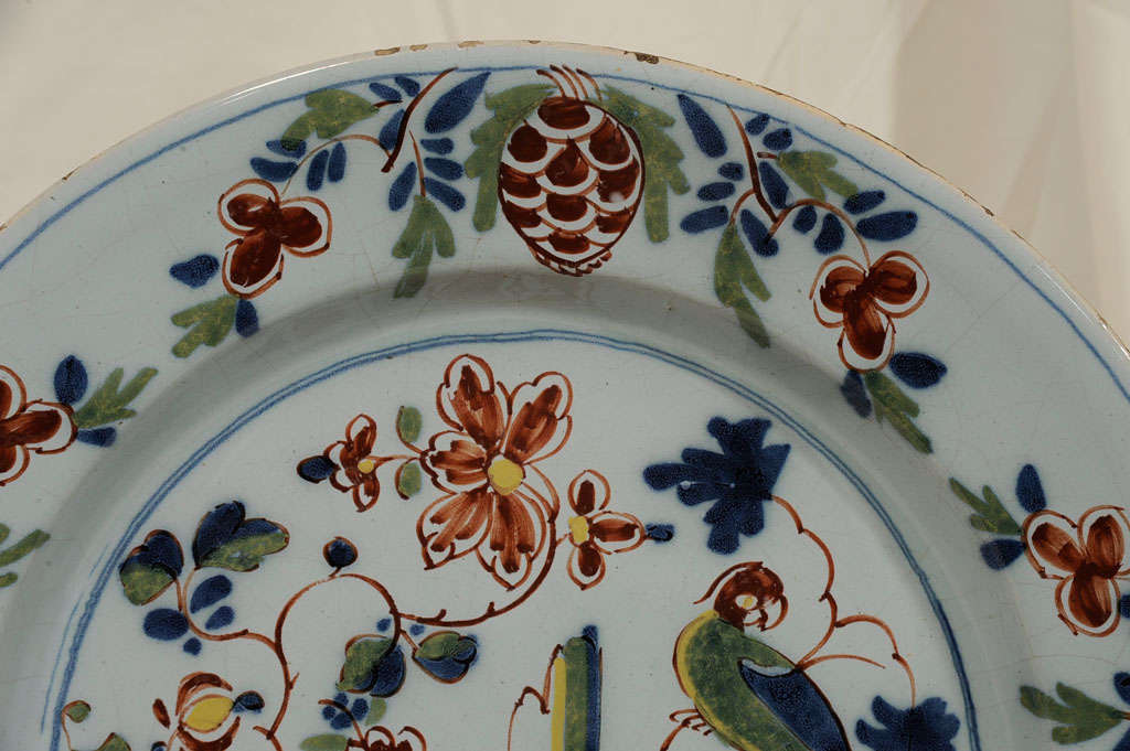 An antique Delft charger with parrot is a delightful example of 18th century Lambeth English Delft. The parrot is resting on a branch at one side of a lush garden with oversized flowers. The scene is surrounded by a border of pinecones which is a
