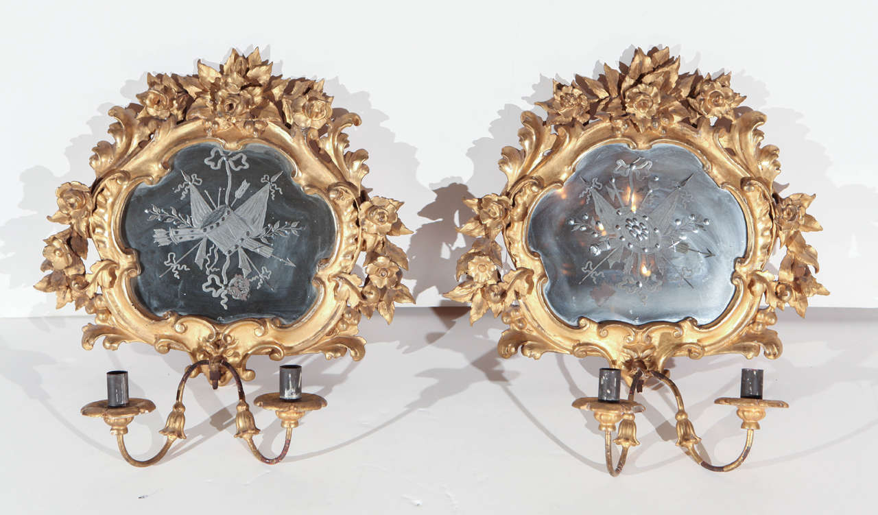 Pair of petite, hand-carved and gilded sconces with inset, etched mirrors featuring flags, drums and arrows.