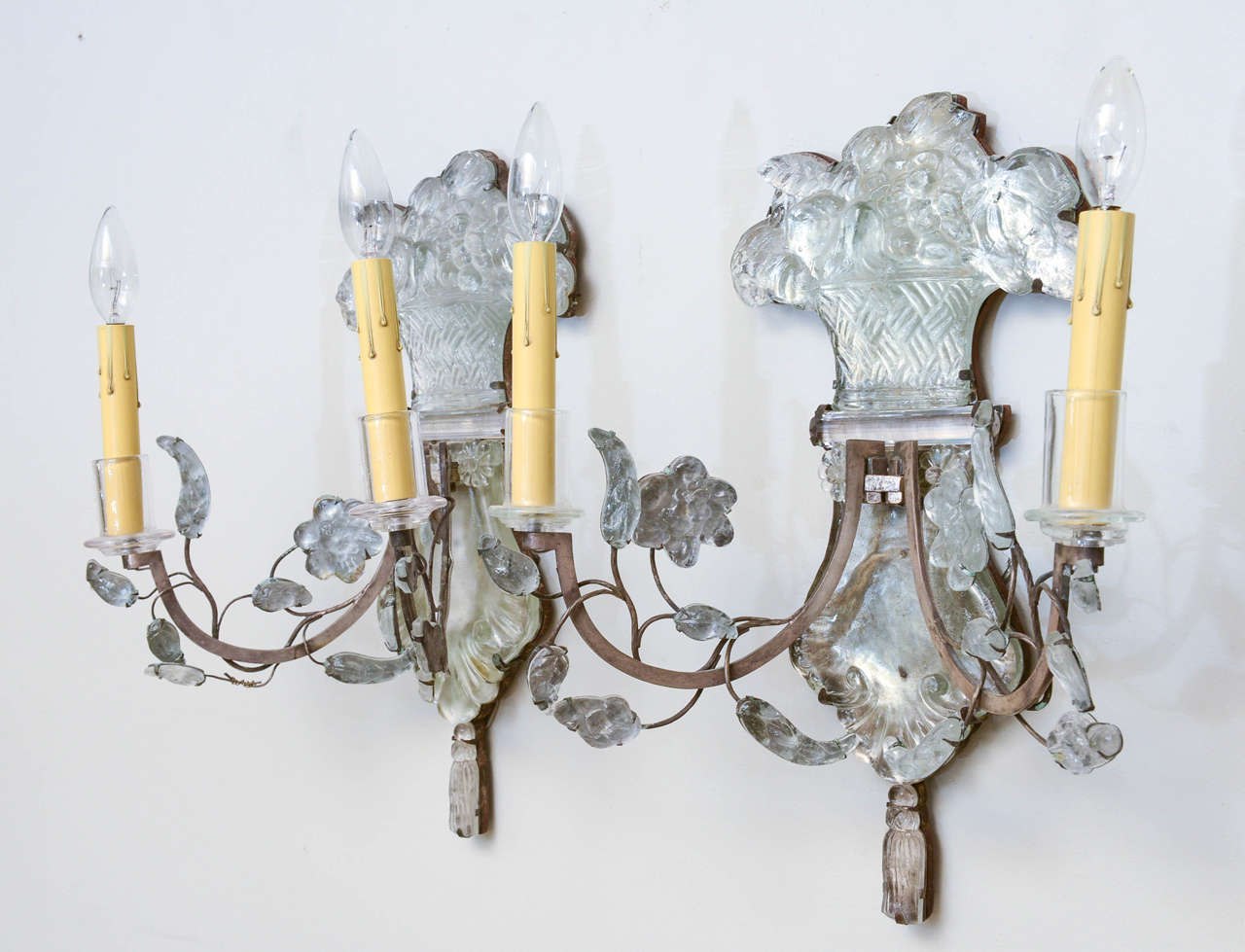 Pair of sconces, likely Bagues; each having two scrolling iron candlearms, draped with crystal leaves and rosettes, its backplate an urn holding a bouquet of flowers, terminating in a tassel.  Stock ID: D9157