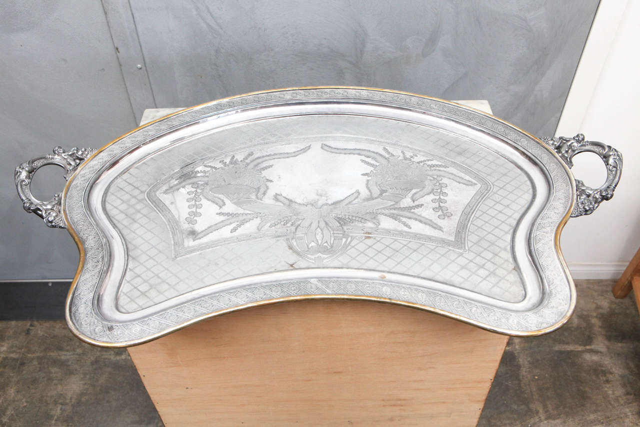 This tray is what is termed a butler tray because it is shaped to fit against the body with two handles. The silver plated tray is beautifully engraved with cornucopias dripping with flora, fauna and fruit. Ribbon bows and a trellis pattern add to