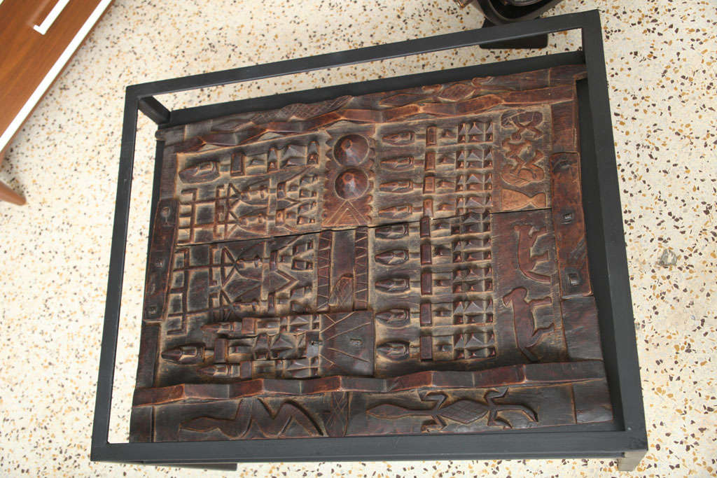 Metal and glass table with carved african panel at stdibs