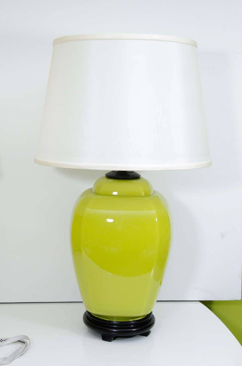 A pair of glass jar lamps in acid green on black wood base with linen shades. These are a nice size and perfect for adding a bright color to a neutral setting.