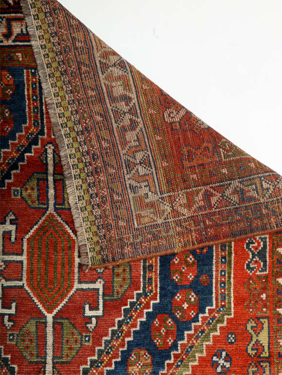 This Persian Qashqai carpet circa 1900 consists of pure handspun wool and organic vegetable dyes. Its pile is hand-knotted and it is in excellent antique condition with rich shades of red, blue, green and navy throughout its double medallion, field