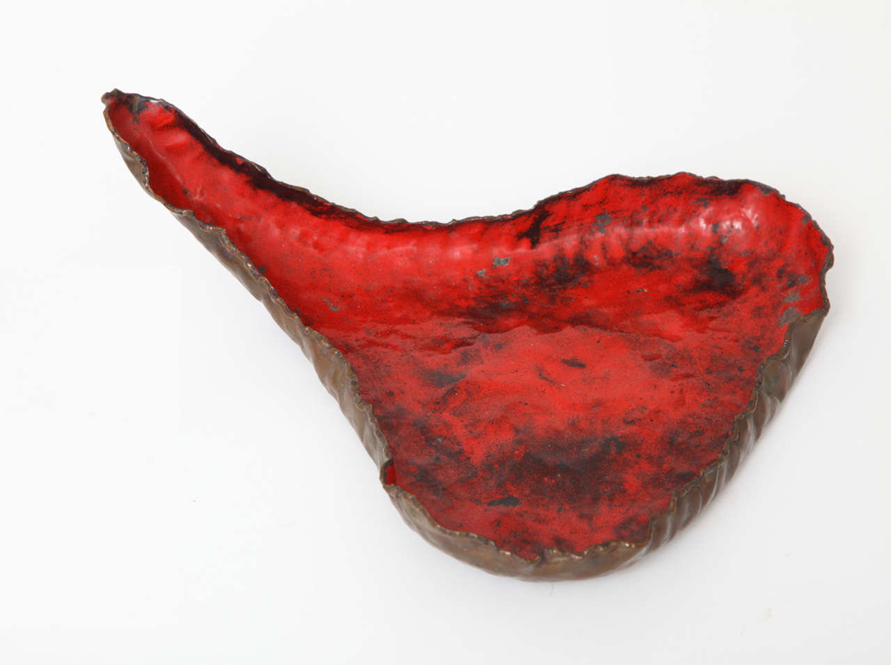 Smoldering, torch-cut form in copper with fiery red glaze to interior. Signed with