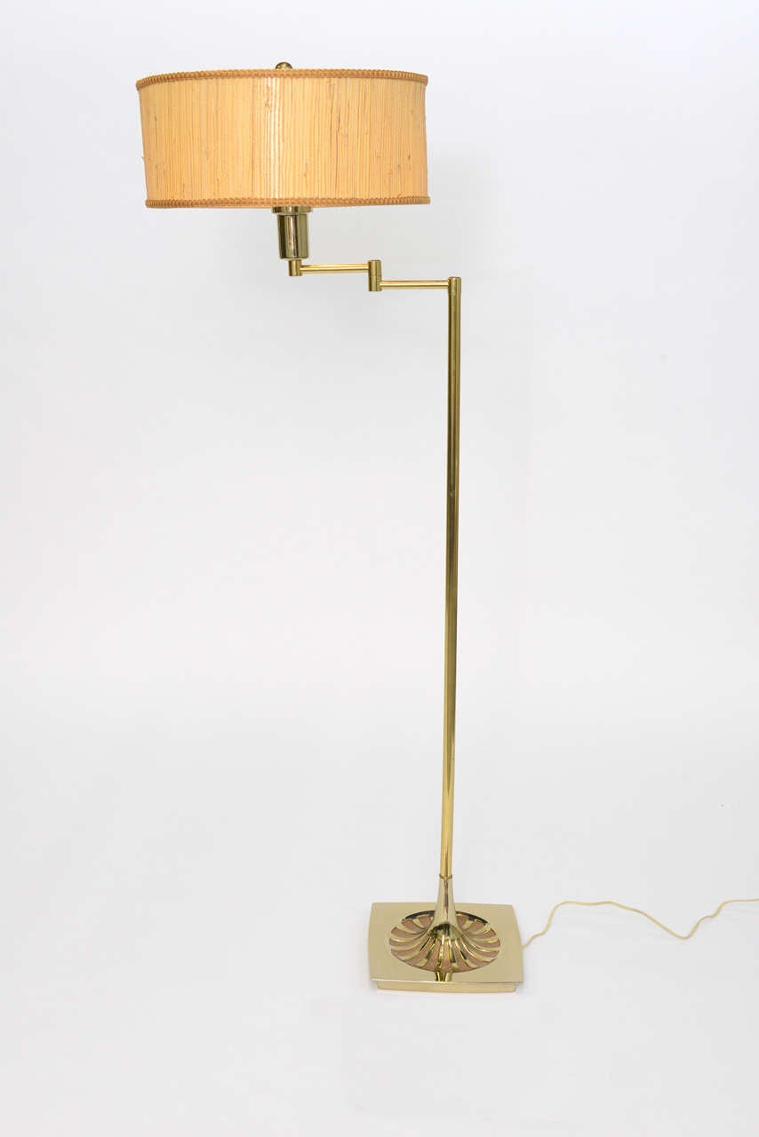 Wonderful brass floor Lamp by Laurel Lamp Co. with a soft edge square base featuring a stylized starburst design. Having a Nessen style articulating arm ending in a milk glass difusser and original grass-cloth barrel shade. Three level medium base