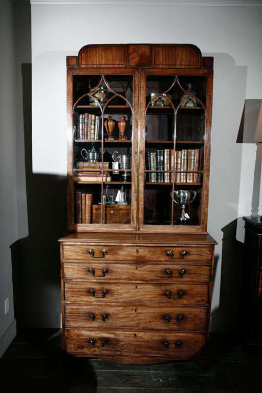 1840s English mahogany secretary bookcase. This handsome secretary has a unique raised cornice with rounded edges above arched muntin pattern glass doors and a secretary fall-front drawer enclosing small drawers and pigeon holes. The lower body