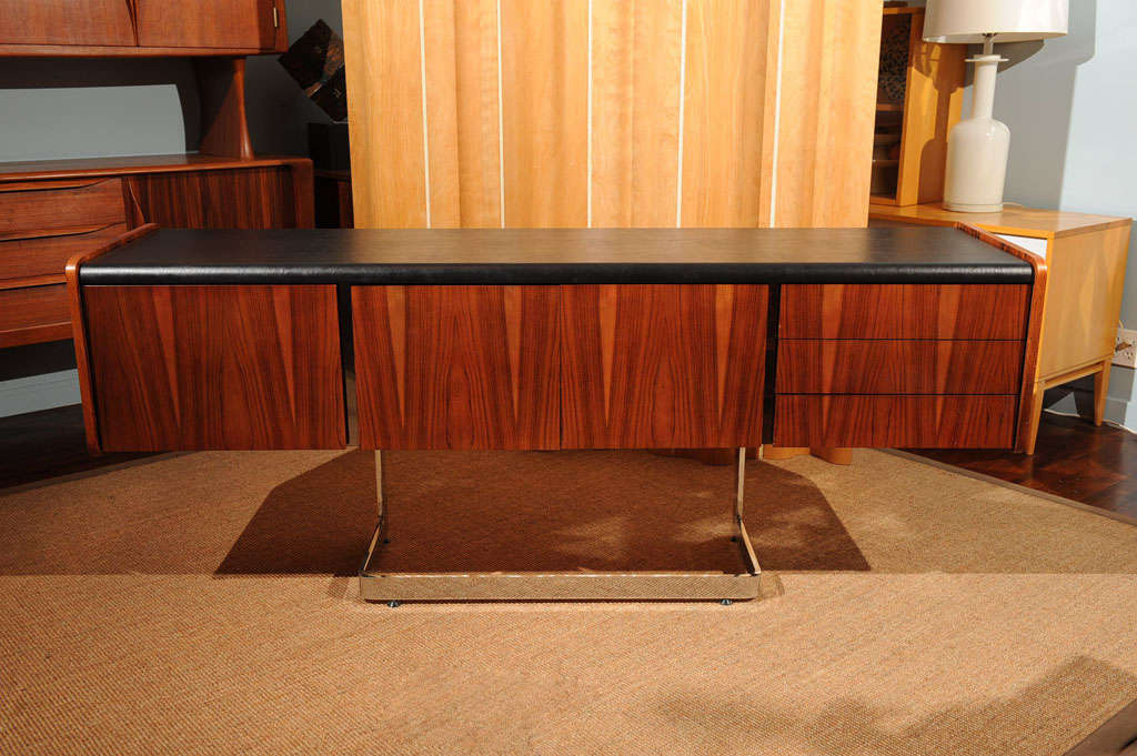 Figured rosewood credenza on a floating chrome base, with a black leatherette top.