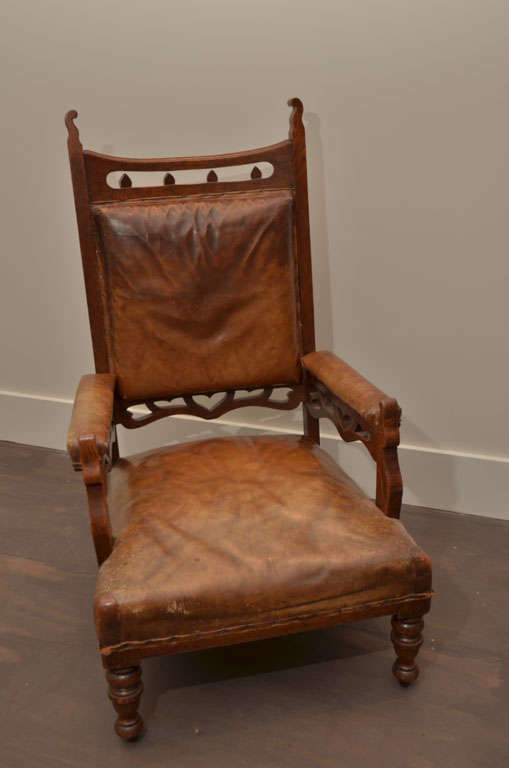 Dramatic oak framed Gothic Style chairs. The original brown leather has wonderful wear and patina. Armchair are sturdy + low seat height makes it very comfortable. <br />