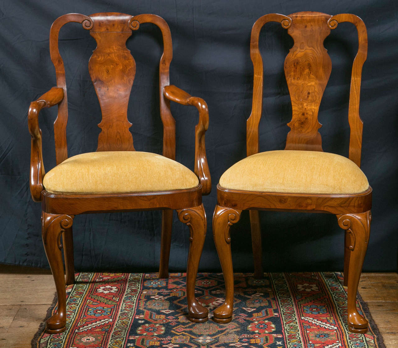A set of ten, two arm chairs and eight side chairs; this set of walnut and walnut burl Queen Anne style dining chairs have curved wood splats that accept the curvature of the spine perfectly. Soft lines and a warm color give these chairs an