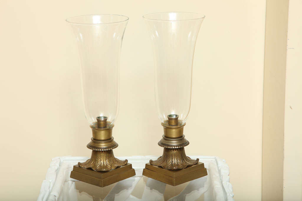 Pair of clear glass single-light hurricane vase table lamps.