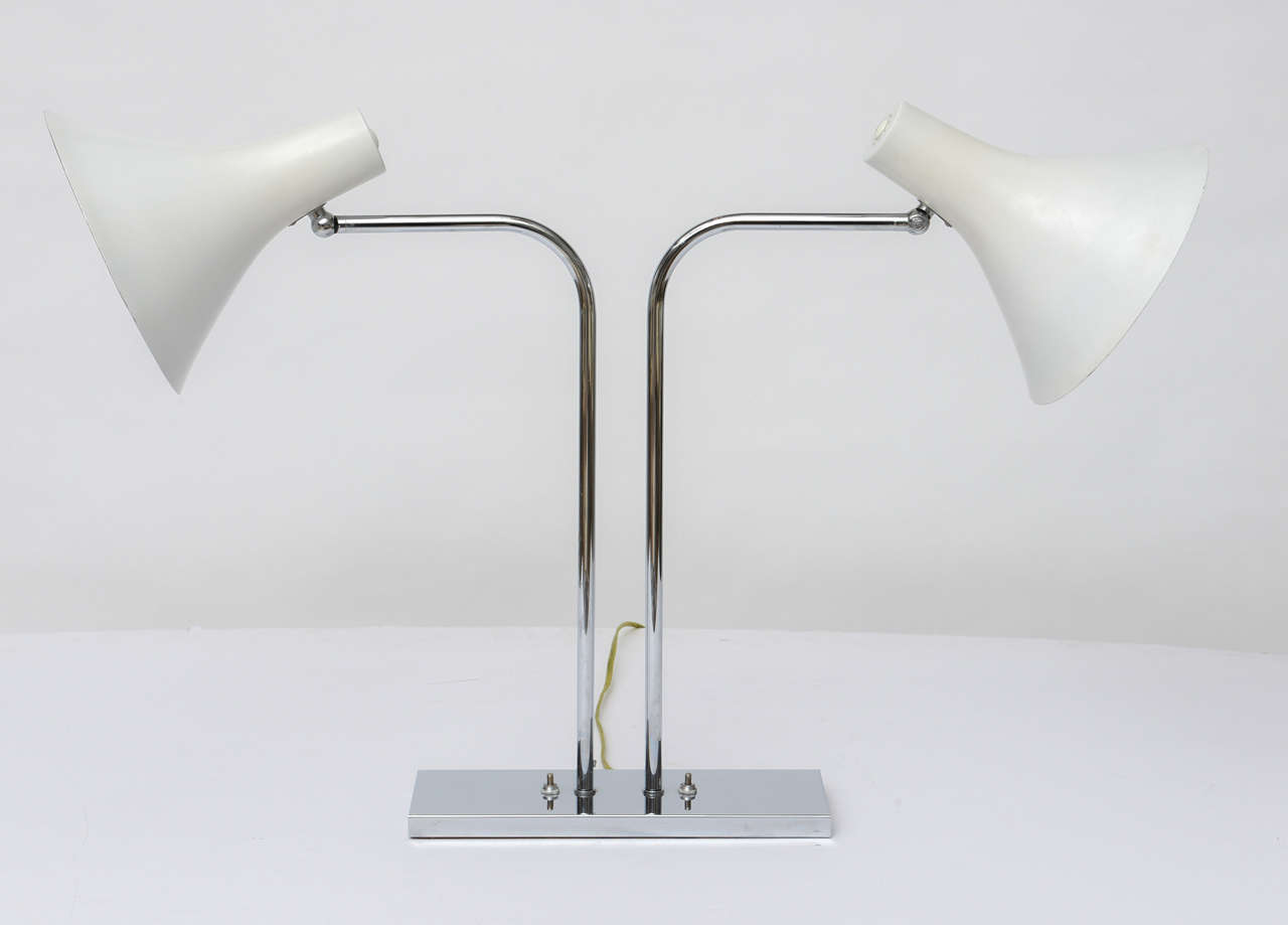 1960's polished chrome double desk lamp by Nessen Studios has swinging arms and lacquered aluminum cone shades that pivot and turn. An elegant and simple classic!