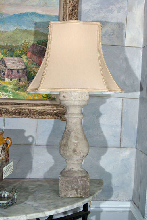 This is a wonderful pair of well-weathered cast stone baluster lamps with cream fabric shades. With their cool stone surface and warm fabric shades, these lamps would look lovely on either side of a modern or antique bed. Rewired for U.S. In great